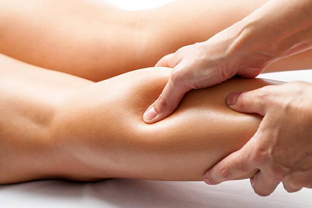 therapeut druck mit den daumen auf weibliche kalbsleder muskeln. - chiropraktik wellness stock-fotos und bilder