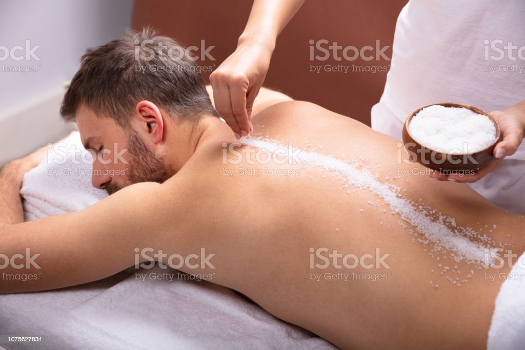 Close-up Of Therapist Hand Applying Salt On Young Man\'s Back