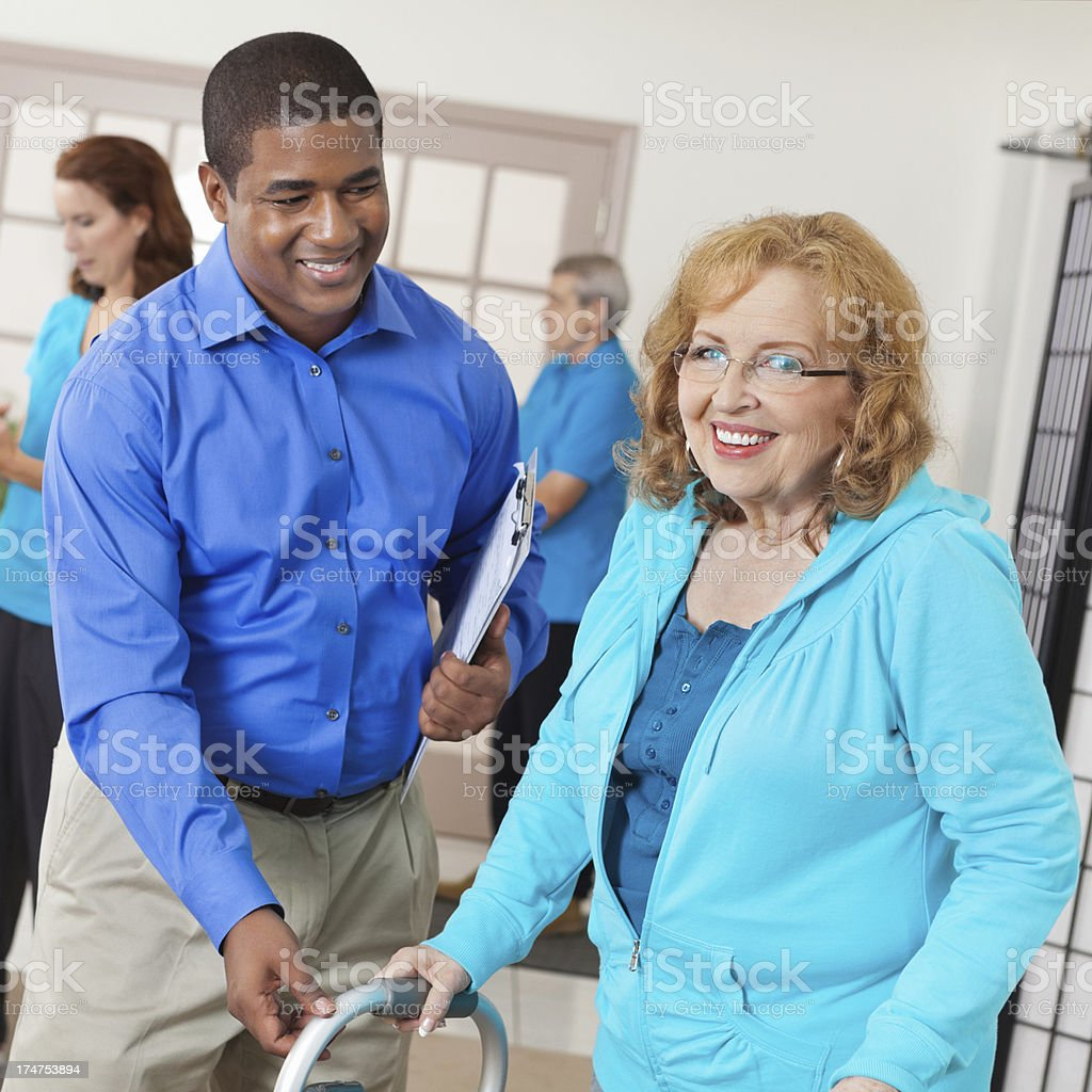 Therapist assisting senior patient with walker in physical therapy gym royalty-free stock photo