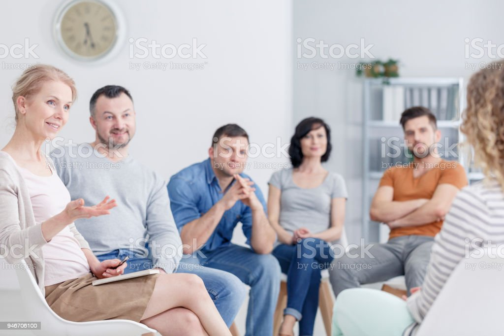 Therapist congratulating woman on progress Therapist congratulating young woman on her progress in therapy and happy family blurry in the background Addiction Stock Photo