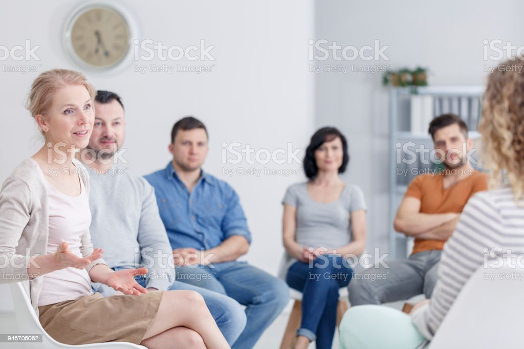 Therapist discussing problems Female therapist discussing problems with her patients during a support group meeting Addiction Stock Photo