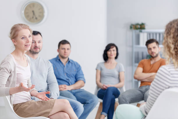 Therapist discussing problems Female therapist discussing problems with her patients during a support group meeting drug rehab stock pictures, royalty-free photos & images