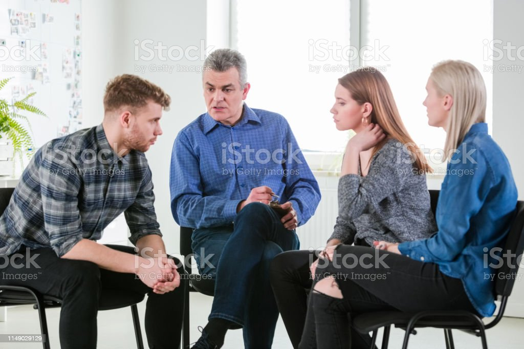 Therapist discussing with university students Mental health professional discussing with university students. Males and females are sitting in lecture hall during meeting. They are in university for group therapy. 18-19 Years Stock Photo