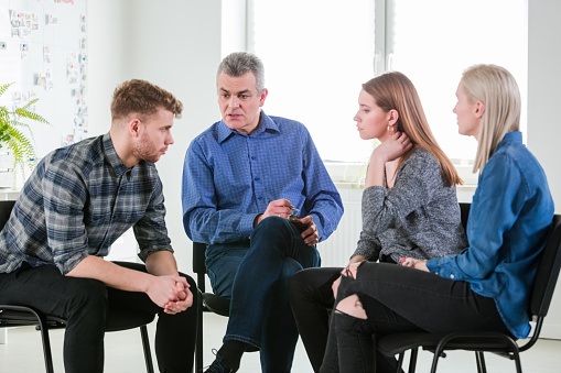 Therapist Discussing With University Students Stock Photo - Download Image Now