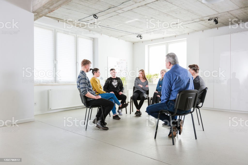 Therapist discussing with young students Mental health professional discussing with university students. Males and females are sitting in lecture hall during meeting. They are in university for group therapy. 18-19 Years Stock Photo