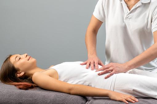 Therapist Doing Abdomen Massage On Little Girl Stock Photo