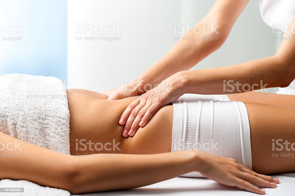 Therapist doing curative belly massage on female patient. stock photo