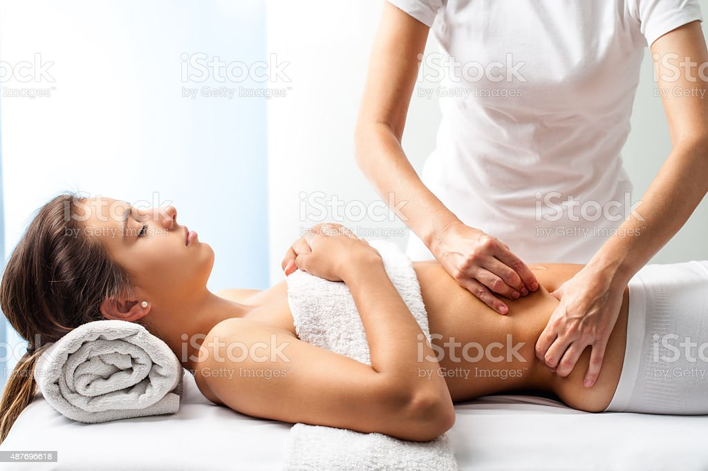 Therapist doing healing massage on female abdomen. stock photo