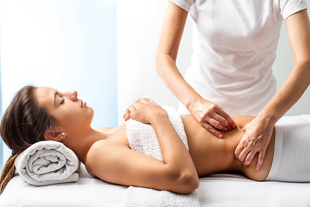 therapist doing healing massage on female abdomen. - human abdomen stock pictures, royalty-free photos & images