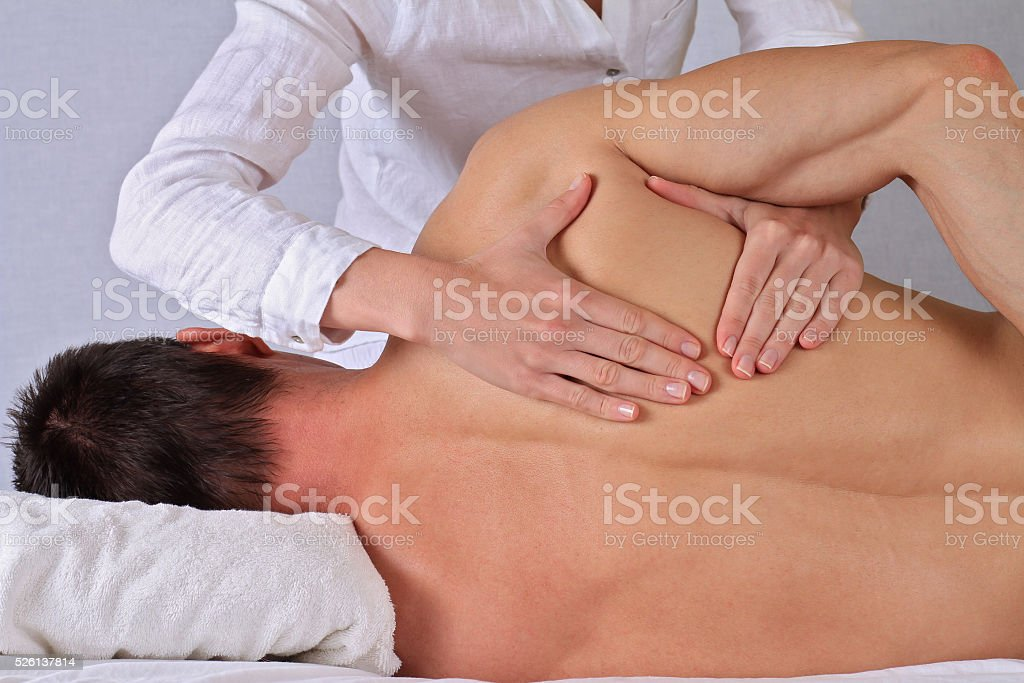 Therapist  doing healing treatment otreatment on man's back . stock photo