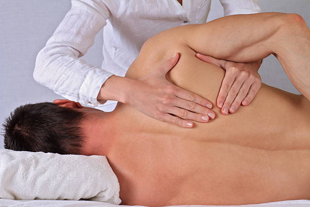 Therapist  doing healing treatment otreatment on man's back . Chiropractic, osteopathy, dorsal manipulation. Therapist  doing healing treatment otreatment on man's back . Alternative medicine, pain relief concept dorsal fin stock pictures, royalty-free photos & images