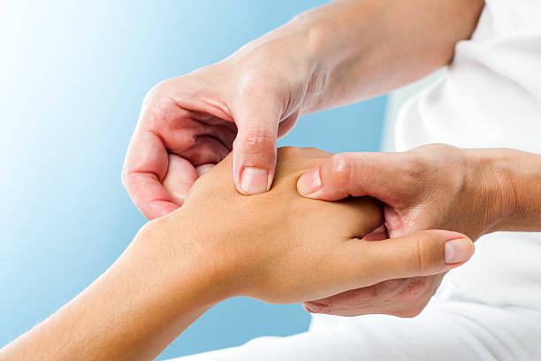 Therapist doing massage on female hand. Macro close up of Therapist doing massage on female hand.Osteopath applying pressure on hand. alternative therapy stock pictures, royalty-free photos & images