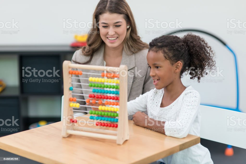 Therapist doing play therapy with young girl stock photo