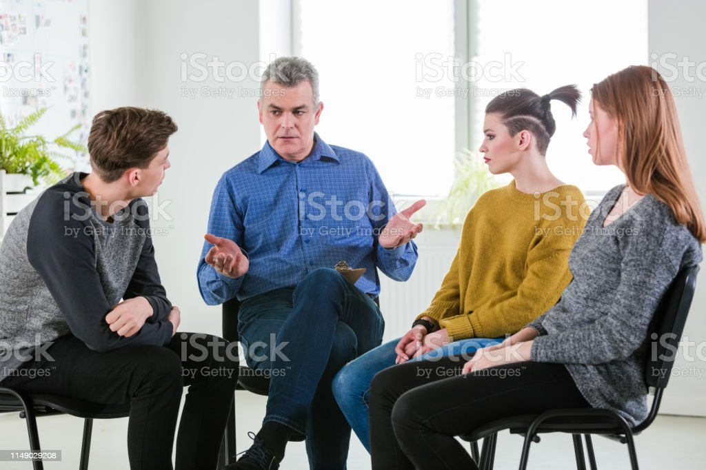 Therapist giving advice to university students Male mental health professional giving advice to university students. Young man and women are listening to social worker during group therapy. They are sitting in lecture hall during meeting. 18-19 Years Stock Photo