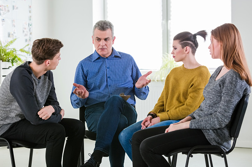 Therapist Giving Advice To University Students Stock Photo - Download Image Now
