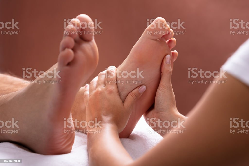Therapist Giving Foot Massage To Man stock photo