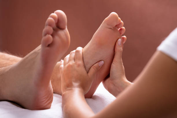 Therapist Giving Foot Massage To Man Close-up Of Therapist Hand Giving Foot Massage To Man foot massage stock pictures, royalty-free photos & images