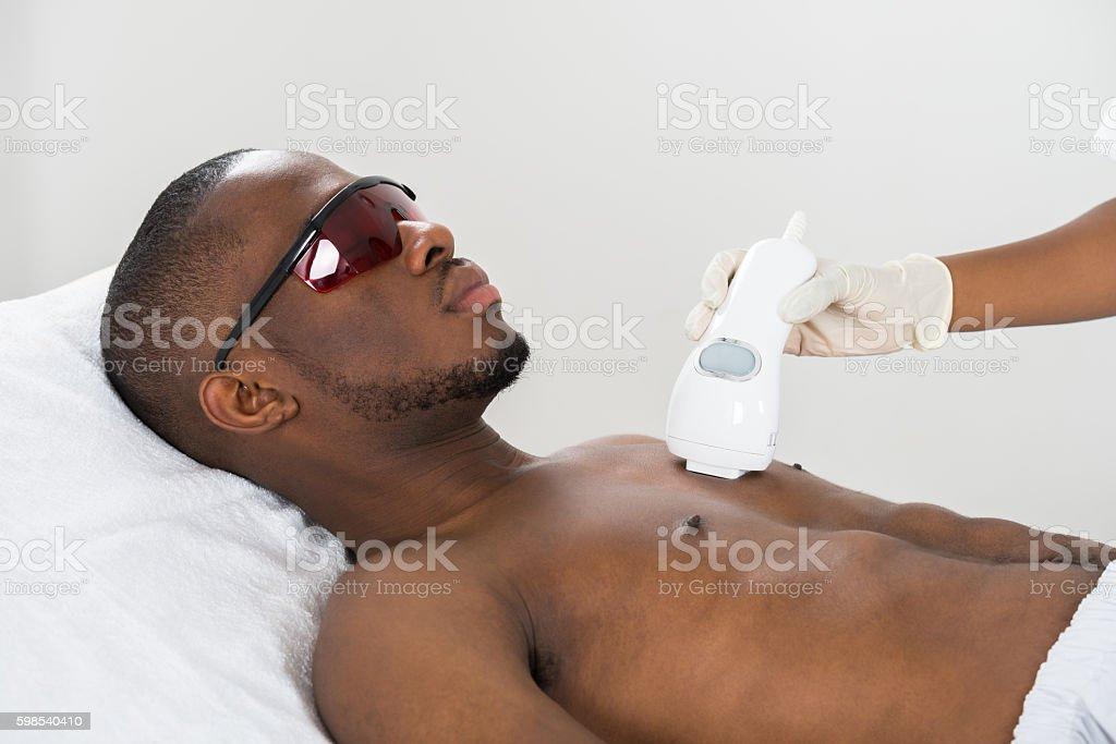 Therapist Giving Laser Epilation On Man's Chest photo libre de droits