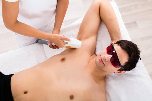 Therapist Giving Laser Epilation Treatment On Man's Armpit stock photo