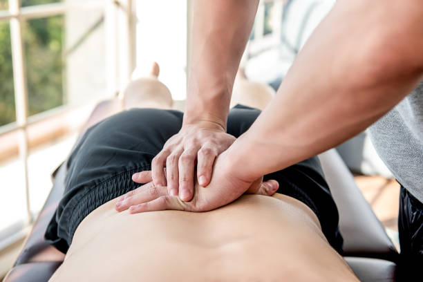 therapist giving lower back sports massage to athlete male patient - sports medicine stock pictures, royalty-free photos & images