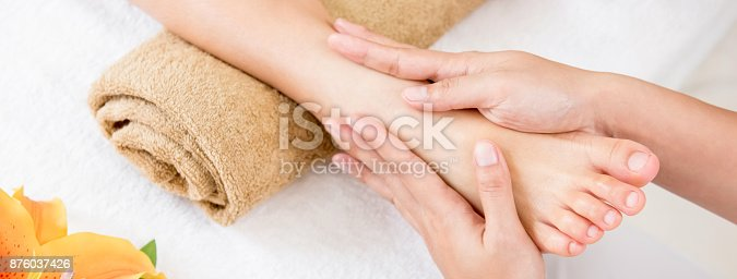 istock Therapist giving relaxing reflexology Thai foot massage treatment to a woman in spa 876037426