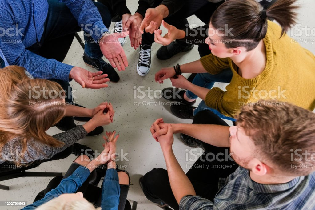 Therapist giving solution to university students High angle view of therapist giving solution to young university students. Mental health professional is sitting with men and women during meeting. They are in group therapy at lecture hall. 18-19 Years Stock Photo