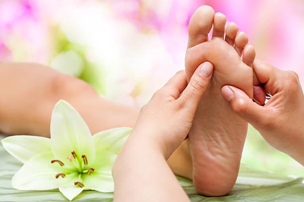 Therapist hands massaging foot. stock photo