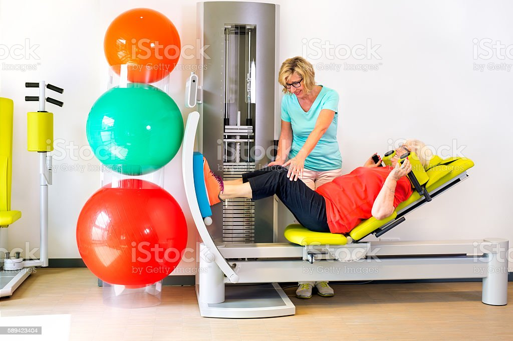 Therapist helps woman strengthen leg muscles. stock photo