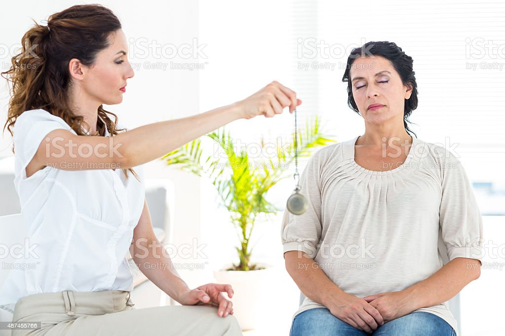 Therapist hypnotizing her patient stock photo