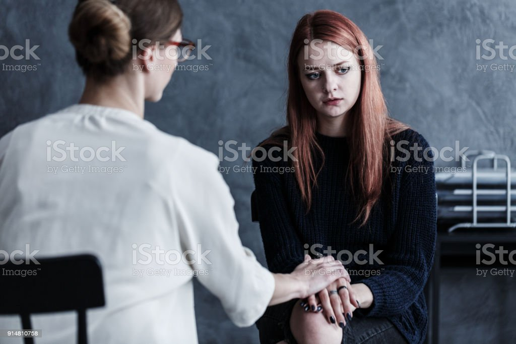 Therapist looking after her patient Dedicated therapist looking after her patient by holding her hand in grey office Adolescence Stock Photo