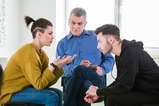 Therapist Looking At Students Discussing Problems Stock Photo - Download Image Now