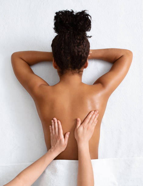 Therapist massaging african woman back, top view stock photo