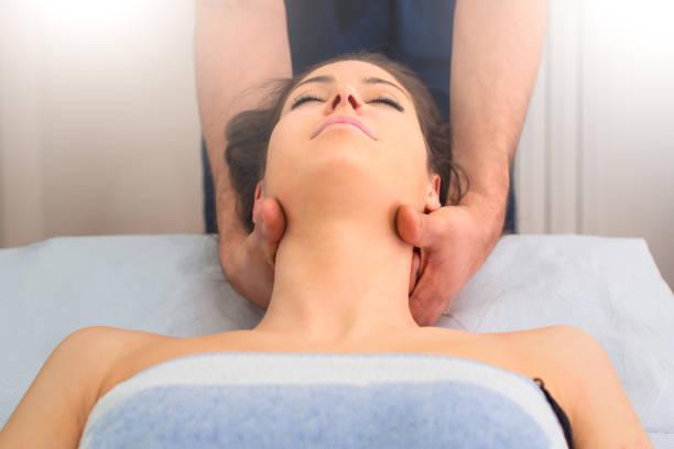 therapist massaging the neck of woman in the by a professional - terapia alternativa foto e immagini stock