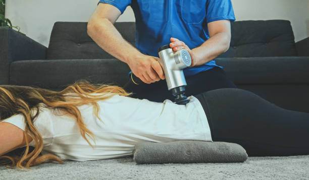 Therapist massaging woman's back at home with massage percussion device. stock photo