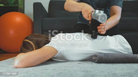Therapist massaging woman's back with massage percussion device at her home.