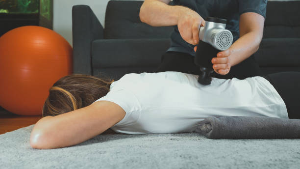 Therapist massaging woman's back with massage percussion device at her home. stock photo