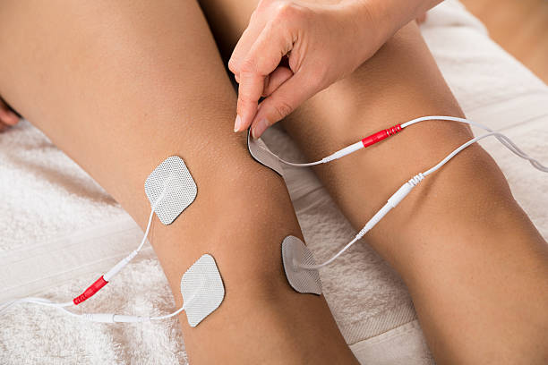Therapist Placing Electrodes On Woman's Knee stock photo
