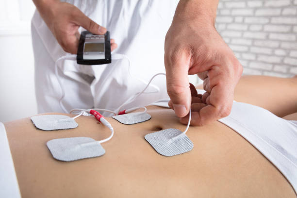 Therapist Placing Electrodes On Woman's Stomach stock photo