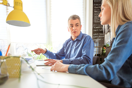 Therapist Pointing At Laptop To Woman In Meeting Stock Photo - Download Image Now