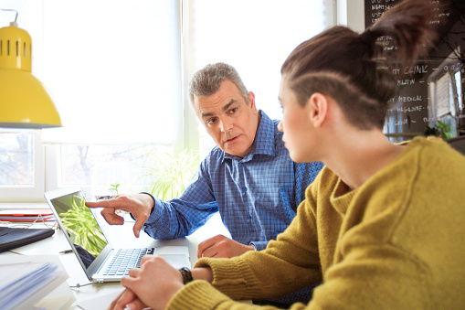 Therapist Pointing At Laptop While Advising Female Stock Photo - Download Image Now