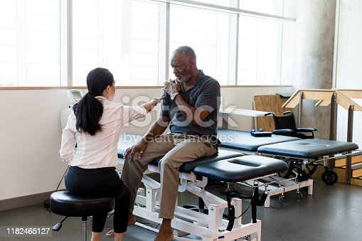 The mid adult female therapist points to confirm the site of pain on the mature man's shoulder.