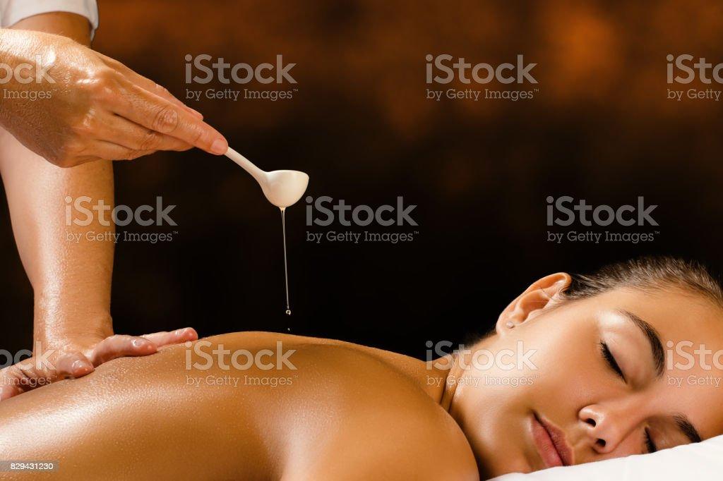 Therapeut Ayurvedische olie gieten op vrouwelijke rug. foto