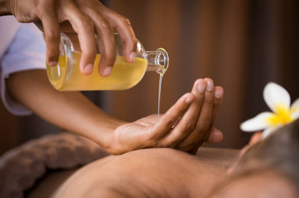 Therapist pouring massage oil at spa Closeup of masseur hands pouring aroma oil on woman back. Masseuse prepare to do oriental spa procedure for relaxing treatment. Therapist doing aromatherapy oil massage on woman body. massaging stock pictures, royalty-free photos & images