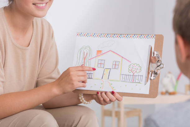 Therapist showing drawing of house stock photo
