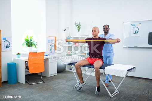 Smiling therapist. Dark-skinned sports therapist smiling while stretching arms of sportsman
