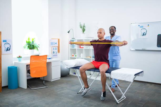 sporcu silah germe sırasında gülümseyen terapist - physical therapy stok fotoğraflar ve resimler