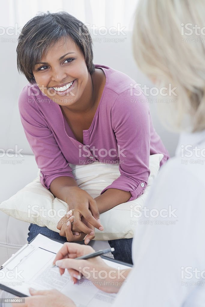 Therapist taking notes on her smiling patient stock photo