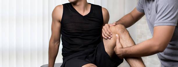 terapeuta tratar heridas de la rodilla del paciente masculino deportista en la clínica - masaje deportivo fotografías e imágenes de stock