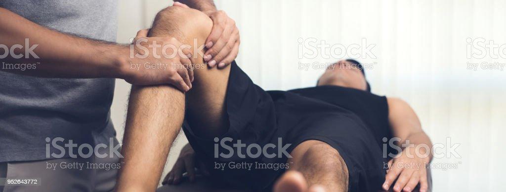 Terapeuta tratar heridas de rodilla de paciente masculino de atleta - foto de stock