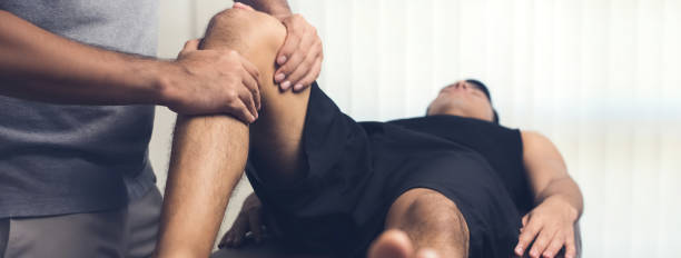therapist treating injured knee of athlete male patient - massaggio foto e immagini stock